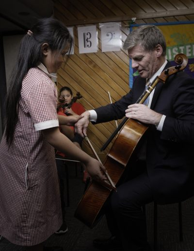 Sistema student, Hadassah, teaches the PM how to play the cello